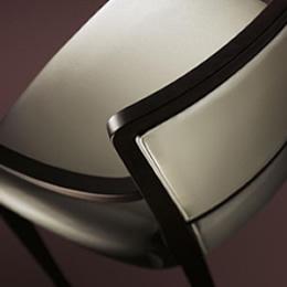Stuhl mit dunklem Holzgestell und weiß gepolsterter Sitzfläche,Rückenlehne und Armlehnen