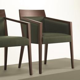 Holzstuhl mit dunklem Holzgestell. Sitzfläche, Rückenfläche und Armlehnen gepolstert mit dunkelgrünem Stoffbezug